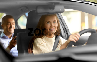 female driver driving car with male passenger