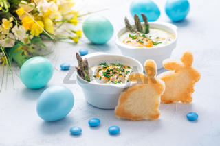 Shirred eggs (Oeuf cocotte) or baked eggs with green asparagus with Easter toast bunny and eggs