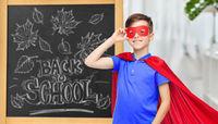 boy in super hero costume over school blackboard