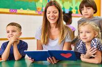 Tagesmutter beim Buch vorlesen für eine Kinder Gruppe