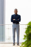 Full length shot of confident African businessman outdoors at rooftop