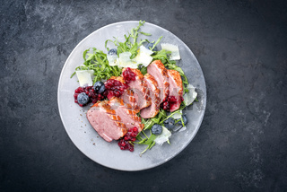 Modern style gourmet duck breast filet with rocket salad and cranberry relish offered as top view on a design plate with copy space