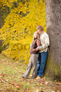 Autumn love couple hugging happy in park