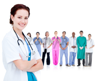 Smiling doctor in front of a team of doctors standing together