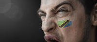 A screaming man with the image of the Tanzania national flag on his face