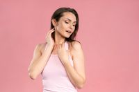 Portrait of a beautiful young female with no makeup, skin care concept, attractive brunette girl on pink background. Human emotions, facial expression concept. Facial expressions, emotions, feelings