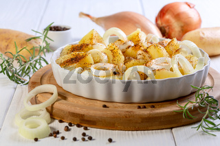 Slices of raw potatoes and onions with spices.