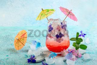 Lemonade with fresh strawberries and flowers.