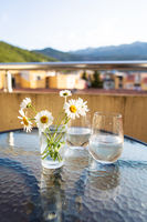 A bouquet of daisies in a glass vase with water stands on a glass table along with a glass of water.