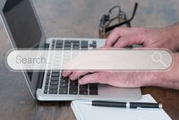 person using laptop computer on wooden table with search engine search box overlay