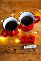 Two cups of coffee in red cups on a background of garlands. Postcard with date and month. Morning breakfast for Valentine's Day. View from above.
