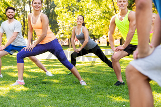 happy people exercising with trainer at park