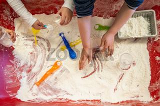 Kindergarten children playing indoor with solids and fluids