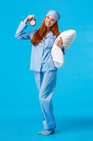 Time to bed. Vertical full-length cheerful lovely, gentle redhead european woman with long red hair, wearing nightwear and sleep mask, holding pillow and red alarm clock, sweet dreams