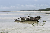 Old wooden fishing boat at low tide in the Indian ocean