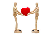 Two wooden dolls/ mannequins holding red heart over a white background