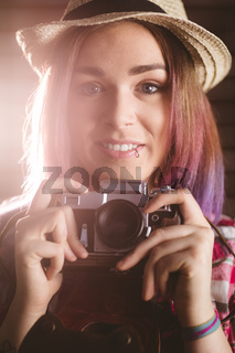 Portrait of smiling woman holding vintage camera