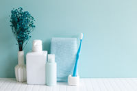 Bathroom bottles, shower towel, toothbrush, vase of plant on white mosaic tile table. blue wall background. Skin care and spa concept. Home interior