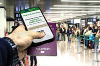 Male hand holding a phone with the European Union vaccination certificate on the screen and a traditional passport inside an airport