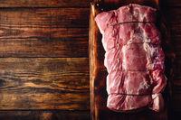 Pork loin joint on rustic cutting board
