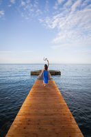 Montenegro, Budva. A girl in a blue dress lies on a wooden pier near the sea, a beautiful sky with clouds. Vacation concept, travel to Europe.