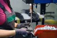 woman wearing mask due to coronavirus pandemic while working in modern metal industry and using drill