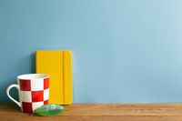 Yellow diary note book with mug cup on wooden desk. blue wall background