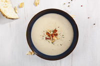Celery cream soup in dark plate on white rustic background from above.