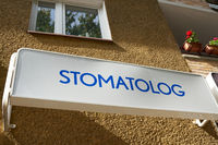 Sign with the inscription Stomatolog (dentist) on a house in the center of Kolobrzeg in Poland
