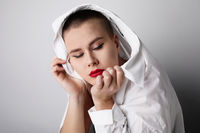 Close-up portrait of bald pretty woman, posing on white wall. Isolated.