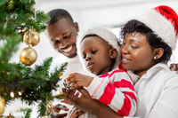 happy family decorating christmas tree at home
