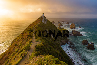 Nugget Point and lighthouse with sunrise at South Island, New Zealand