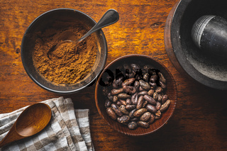 Roasted cocoa beans and cocoa powder in bowl