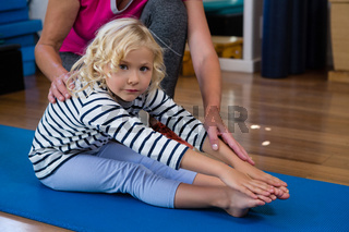 Female physiotherapist helping girl patient in performing stretching  exercise on exercise mat