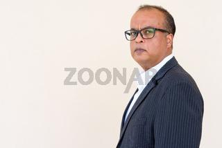 Portrait of Indian businessman against plain wall outdoors