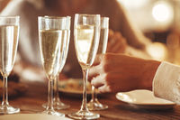 Unrecognizable female taking wineglass with champagne while standing near banquet table with burning candles