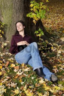 junge Frau schläft unter Baum