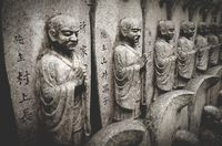 Selective focus on stone buddhist statues in a line at the Daisho-in temple at Miyajima, Japan