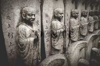 Selective focus on stone buddhist statues in a line at the Daisho-in temple at Miyajima, Hiroshima, Japan