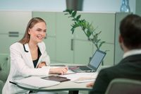 Smiling professional HR agent making a job interview to a applicant in the bright modern office. Young woman interviewing young freelancer for job position