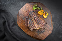 Traditional barbecue dry aged wagyu porterhouse beef steak offered with paprika and chili as top view on modern design wooden board