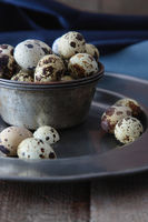 Closeup of quail eggs with plates on wood table