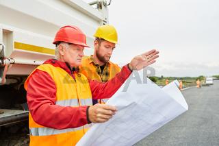 Architekt und Arbeiter mit Lageplan für die Bebauung