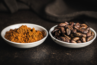Cocoa powder and cocoa beans in bowl.