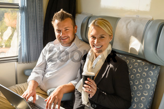 Woman and man sitting in train smiling