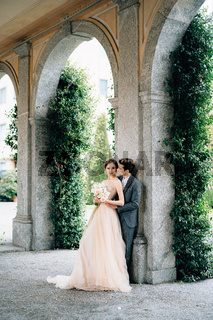 Serious newlyweds are hugging leaning against the arch against the backdrop of greenery. Lake Como