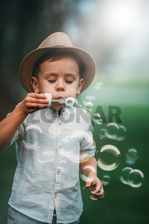 The child diligently blows a lot of soap bubbles in the park.