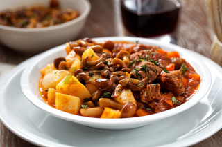 Hot stew with mushrooms and potatoes on a plate.