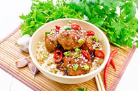 Meatballs in sweet and sour sauce with rice on bamboo napkin