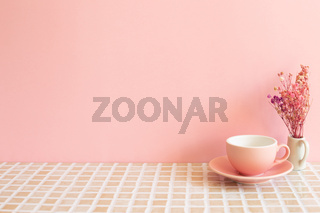 Coffee cup and vase of dry flowers on mosaic tile table. pink wall background. Home interior
